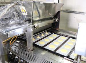 「虎焼」生産の様子。銅板に自動で紙を敷いて生地を充填する