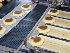 焼成後自動で紙を剥がし、粒餡を絞って合わせる